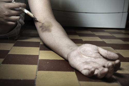 Hand on the floor with syringe