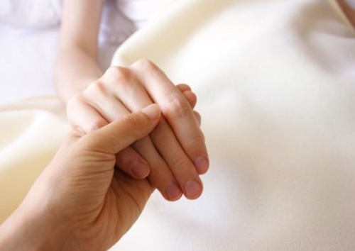 Man holding a womans hand in the hospital